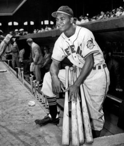 Larry Doby, first black in the American League, poses proudly in his Cleveland Indians uniform in the dugout in Comiskey Park in Chicago, Ill., on July 5, 1947. (AP Photo)